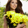 .Beautiful woman relaxing in garden. Holding yellow flowers — Stock Photo