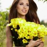 .Beautiful woman relaxing in garden. Holding yellow flowers — Stock Photo