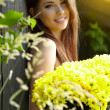 .Beautiful woman relaxing in garden. Holding yellow flowers — Stock Photo #6219853