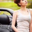 Royalty-Free Stock Photo: Sexy woman posing next to cabrio car