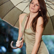 Beautiful woman holding umbrella out in the rain - Stock Photo