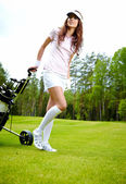 Female golf player walking on fairway with their golf trolleys — Stock Photo