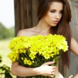 Closeup portrait of cute young girl with yellow flowers smiling — Stock Photo #6262479