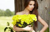 可爱的年轻女孩与黄色的花朵微笑的特写肖像 — 图库照片