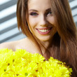 Young woman holding yellow flowers — Stock Photo