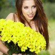 Young woman holding yellow flowers — 图库照片