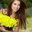 Young woman holding yellow flowers — Stock Photo #6283374