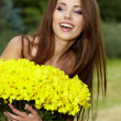 Young woman holding yellow flowers — ストック写真