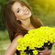 Young woman holding yellow flowers — Stock fotografie