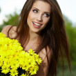 Young woman holding yellow flowers — Foto Stock
