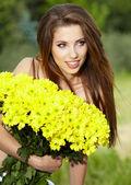 молодая женщина холдинг желтые цветы — Стоковое фото