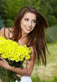 Donna giovane azienda giallo fiori — Foto Stock