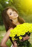Jonge vrouw bedrijf gele bloemen — Stockfoto