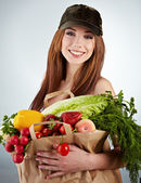 Portrait of happy woman holding a shopping bag full of groceries — Stock Photo