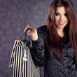 Portrait of young beautiful women with her shopping bags (retro - Stock Photo