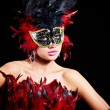 Beautiful young woman in carnival mask and feather boa. — Stock Photo