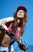 Young woman on a bicykle outdoors smiling — Stock Photo