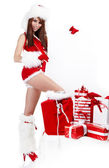 Sexy christmas girl smiles and holding a gift in packing — Stockfoto