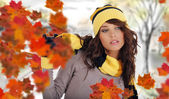 Beautiful woman wearing hat and gloves and maple leaves — Stock Photo