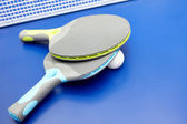Two table tennis or ping pong rackets and balls on a blue table — Stock Photo