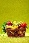Basket full of fresh produce. green background — Stock Photo