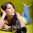 Woman with camera on green spring background - Stock Photo