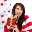 Beautiful woman with gift next to white christmas tree — Stock Photo #6688821