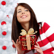 Beautiful woman with gift next to white christmas tree — Stock Photo #6688849