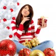 Beautiful woman with gift  next to white christmas tree — Stock Photo