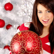 Beautiful woman with decoration next to white christmas tree — Stock Photo
