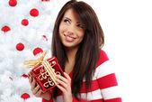 Beautiful woman with gift next to white christmas tree — Stock Photo