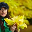 Fashion woman in autumn park holding yellow leaf — Stock Photo #6691685
