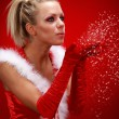 Attracive sexy girl in santa cloth blowing snow from hands. — Stock Photo