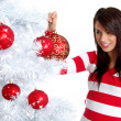 Young Woman decorating white christmas tree — Stock Photo #6700655