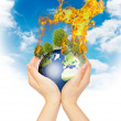 Womanish hands holding burning Earth. — Stock Photo