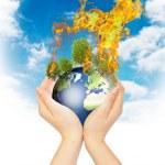 Womanish hands holding burning Earth. — Stock Photo