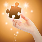 Womanish hand with a orange shining piece of puzzle — Stock Photo