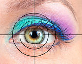 Eye with pink, green make-up and target — Stock Photo