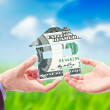 The House made from USD in the Hand against the sunny blue sky — Stock Photo