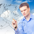 Businessman drawing plane and world map — Stock Photo #6669700