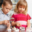 Children are considering magnifying glass collection of stones — ストック写真 #5610353