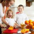 Mother with children squeezed orange juice — Stock Photo