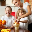 Mother with children squeezed orange juice — Stock Photo #6586010