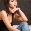 Young woman sitting on a sofa - Stock Photo