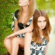 Two beautiful girls sit on stub — Stockfoto