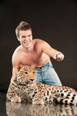 Young man and spotty leopard — Stock Photo