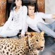 Mature woman and young man with spotty leopard - Stock Photo