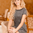 Young woman sits in beautiful armchair — Stock Photo #5556632