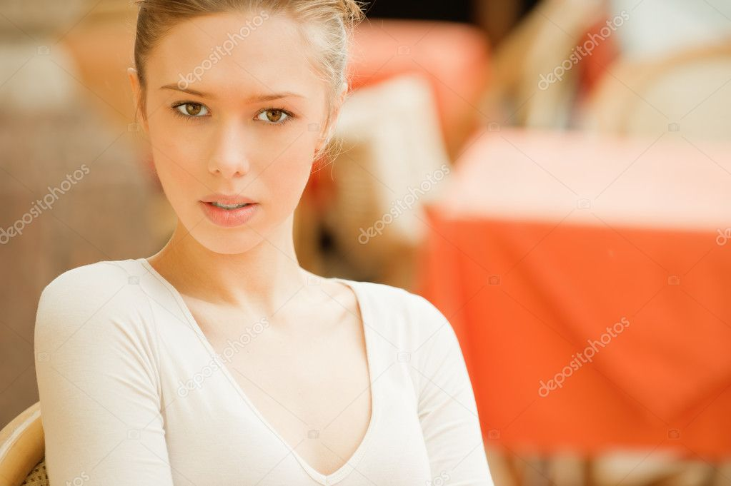 Sad girl sits at little table and looks in camera. — Stock Photo #5637445