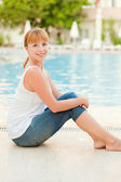 Smiling woman in jeans nearby pool — Stock Photo